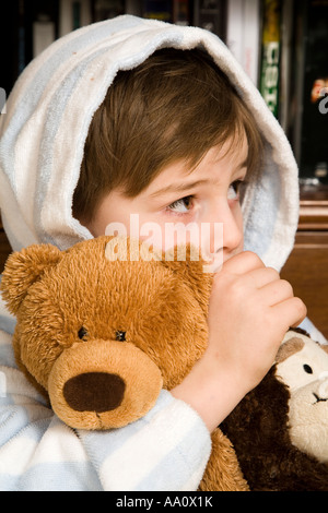 Young boy in a dressing gown sucking his thumb and holding his teddy bear Stock Photo