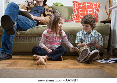 Brother and sister sitting on floor - Stock Photo