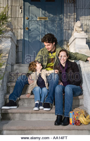Family sitting on steps - Stock Photo