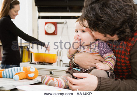 Baby and parents in kitchen - Stock Photo