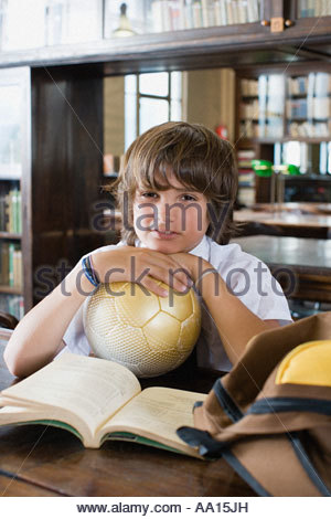 Boy in library with football - Stock Photo
