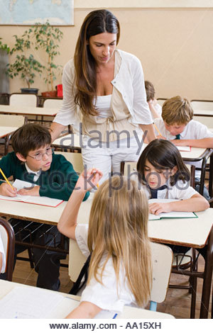 Teacher and pupils in classroom - Stock Photo
