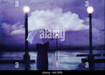 Woman under umbrella walking on bike path at beach rainy evening storm cloud reflected in puddles - Stock Photo