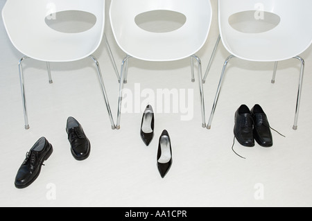 Shoes and chairs in a row - Stock Photo