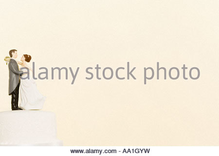 Wedding figurines on top of cake - Stock Photo