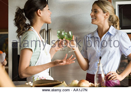 Women in kitchen having wine - Stock Photo