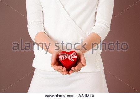 Woman holding heart shaped box - Stock Photo