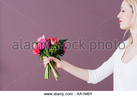 Young woman giving flowers - Stock Photo