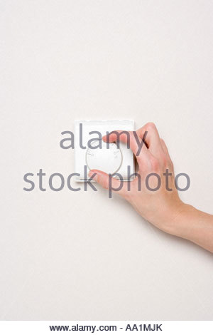 Person turning thermostat - Stock Photo