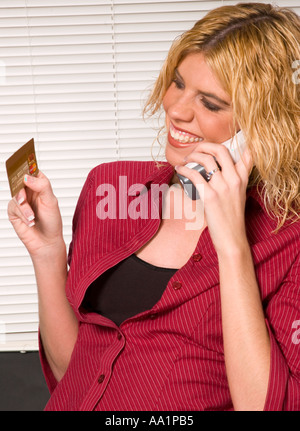 Young woman smiles and gives credit card number over phone USA - Stock Photo