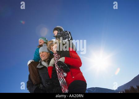 Parents Giving Children Piggyback Rides - Stock Photo