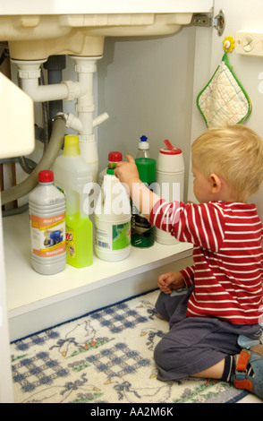 Child reaching for bottles of cleaning fluids under the sink in the kitchen - Danger / accidents concept - Stock Photo