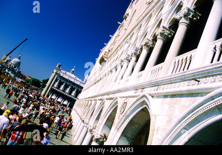 Italy, Venice, Palazzo Ducale Doges Palace, elevation of white stone building arched with columns, tourists in square - Stock Photo