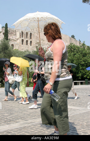 tourists with umbrella under Acropolis Greece Athens heatwave 21 June 2007 - Stock Photo