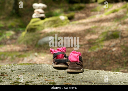 child shoes on the top of a stone - Stock Photo