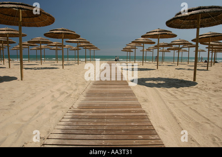 People stroling on the beach behind Parasols and a board walk in Rimini Northern Italy - Stock Photo