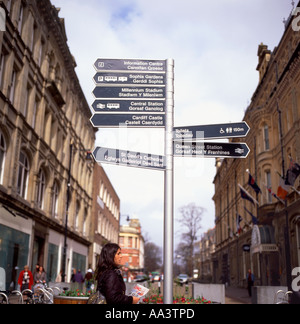 A woman waiting on Queen Street by directional street signs in Cardiff Wales UK  KATHY DEWITT - Stock Photo