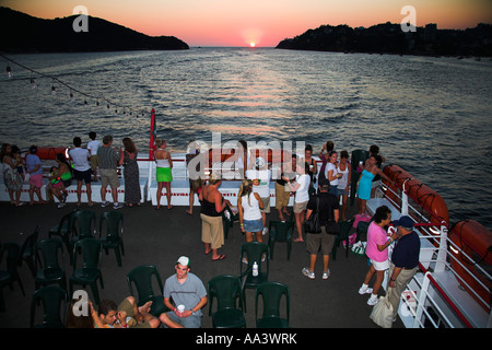 Tourists on deck of cruise ship at sunset in Acapulco Bay, Acapulco, Guerrero State, Mexico - Stock Photo
