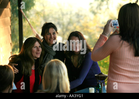 Three smiling and attractive women have their photograph  taken by a daughter with a digital camera - Stock Photo