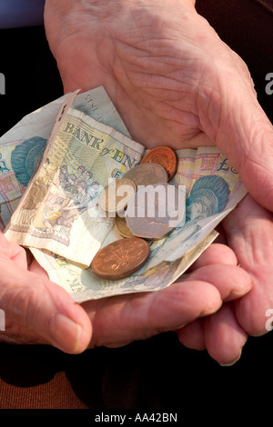Elderly womans hand holding british coins bank notes - Stock Photo