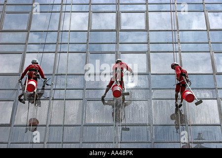 High rise window cleaners work suspended on ropes Orchard Road Singapore - Stock Photo