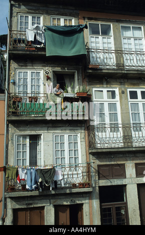 Old flat apartment on the waterfront in Porto Oporto with tenant on the balcony - Stock Photo