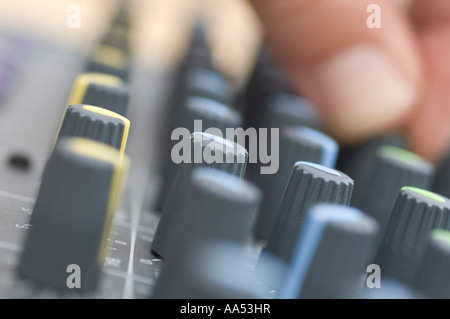 A mixing desk in a studio being adjusted by sound engineer. Picture by Jim Holden. - Stock Photo