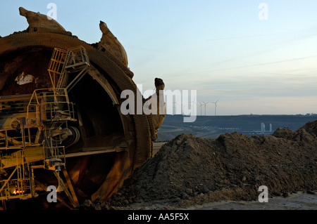 Garzweiler II open cast coal mine near Cologne, Germany; close up of bucketwheel excavator with wind farm in background. - Stock Photo