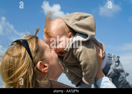 Horizontal close up of a young mother playing with her baby boy, making him laugh by rubbing noses with him in the - Stock Photo