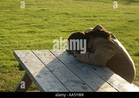 ANG104017 Indian Lady sitting on bench and resting her head on table Sweden Model Release 468 - Stock Photo