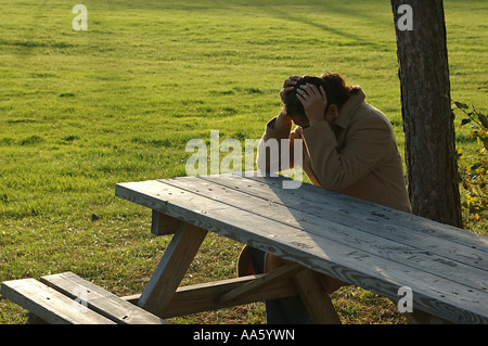 ANG104018 Indian Lady sitting on bench and resting her head on table Sweden Model Release 468 - Stock Photo