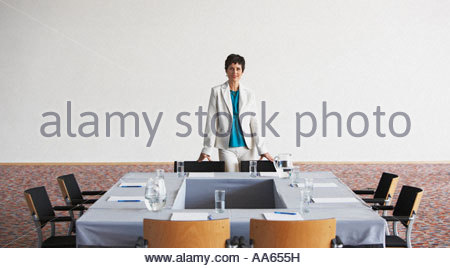 Businesswoman preparing meeting room and table - Stock Photo