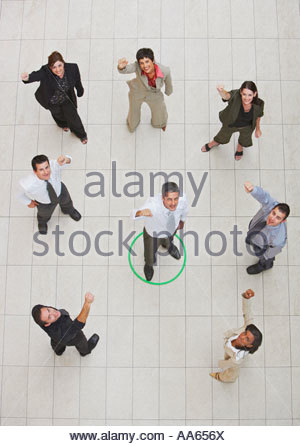 Aerial view of businessman standing in circle with businesspeople cheering - Stock Photo