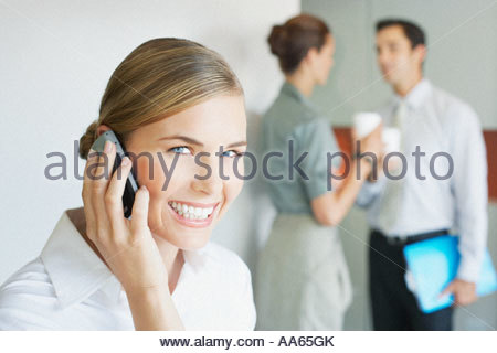Businesswoman talking on cell phone with colleagues in background - Stock Photo