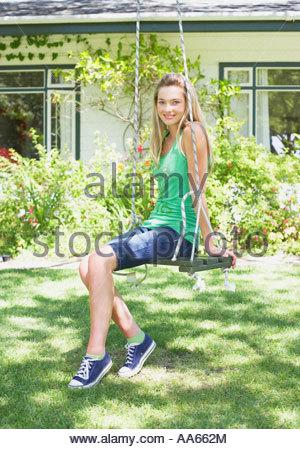 Teenage girl on swing outdoors in yard - Stock Photo
