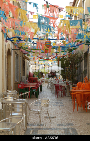 Festive Pedestrianised Street Decorated with Coloured Lights and Bunting at Silves Algarve Portugal - Stock Photo