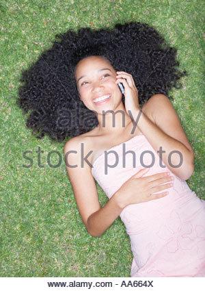 Overhead view of teenage girl laying on grass with cell phone - Stock Photo