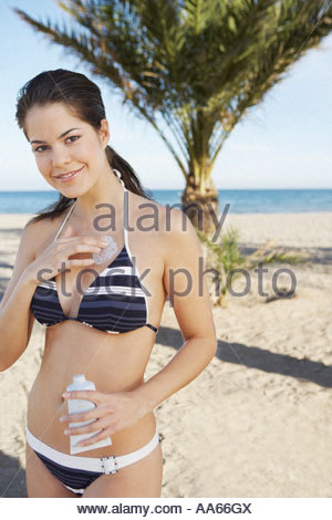 Woman on a beach applying sunblock lotion to herself - Stock Photo