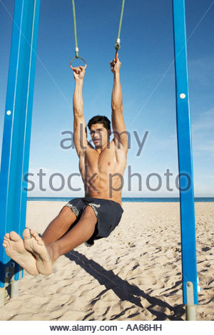 Man on a beach working out on exercise rings apparatus - Stock Photo