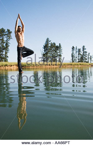 Man doing yoga on water with trees - Stock Photo