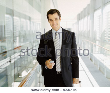 Male business traveler with cell phone smiling - Stock Photo