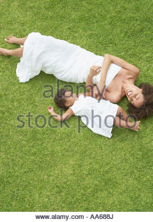 Mother and daughter on grass in summer from above - Stock Photo