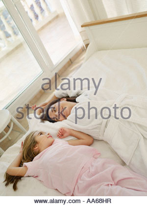 Mother lying on bed with young daughter - Stock Photo