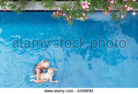 Mother with baby in pool with flowers - Stock Photo