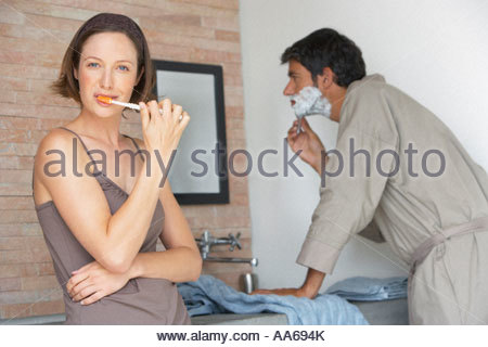 Man shaving and woman brushing teeth - Stock Photo