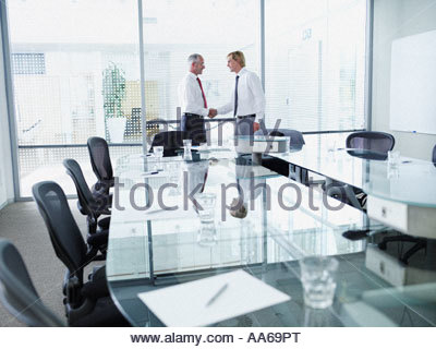 Two businessmen meeting and shaking hands in a boardroom - Stock Photo