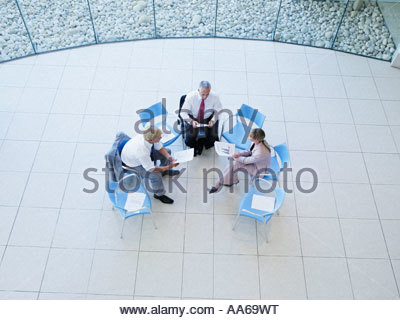 Aerial view of three office workers meeting in a rotunda - Stock Photo
