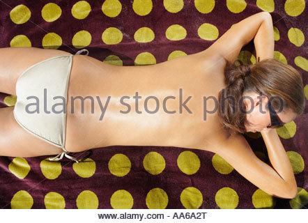 Woman lying down on beach towel with suntan lotion on back - Stock Photo