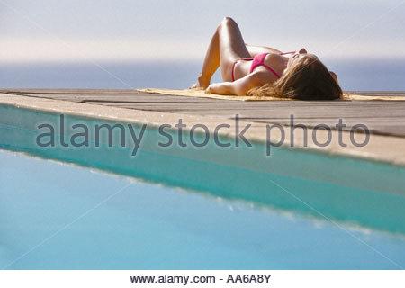 Woman sunbathing on pool deck - Stock Photo