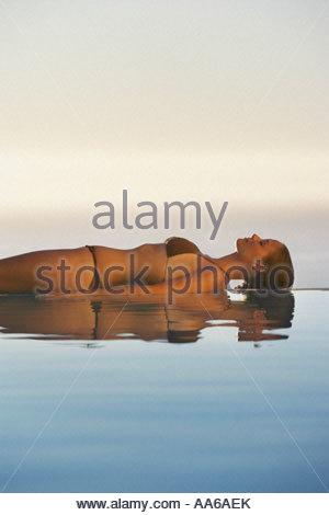 Woman lying down in bikini on edge of infinity pool - Stock Photo